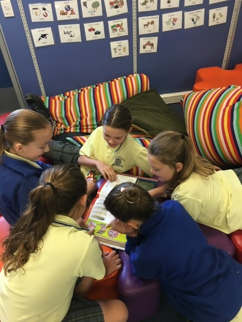 Girls reading on cushions
